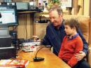Tim Allen (L) as Mike Baxter, KAØXTT, sits in his ham shack with Flynn Morrison, who plays his grandson on the sitcom. [Photo courtesy of John Amodeo, NN6JA]