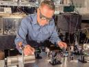 NIST physicist Dave Howe aligns a laser beam to pass through a tiny glass cell of rubidium atoms inside the cylindrical magnetic shield. The atoms are the heart of an atomic magnetometer demonstrated as a receiver for digitally modulated magnetic VLF signals. NIST scientists hope further advances in receivers and transmitters could improve communication and mapping indoors at long range, in urban canyons, underwater, and underground. [NIST photo]